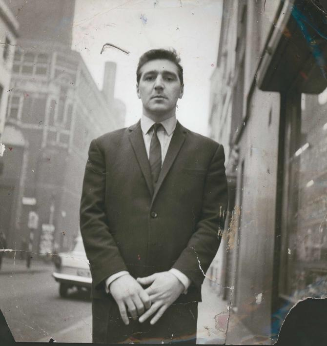 Photograph of George Dyer standing on a street in Soho, by John Deakin